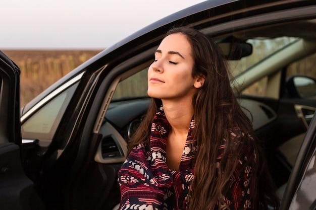 Zijaanzicht van vrouw genieten van natuur in de auto