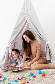 Zijaanzicht van vrouw het spelen met jong meisje in tent