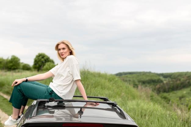 Zijaanzicht van vrouw het stellen in aard bovenop auto