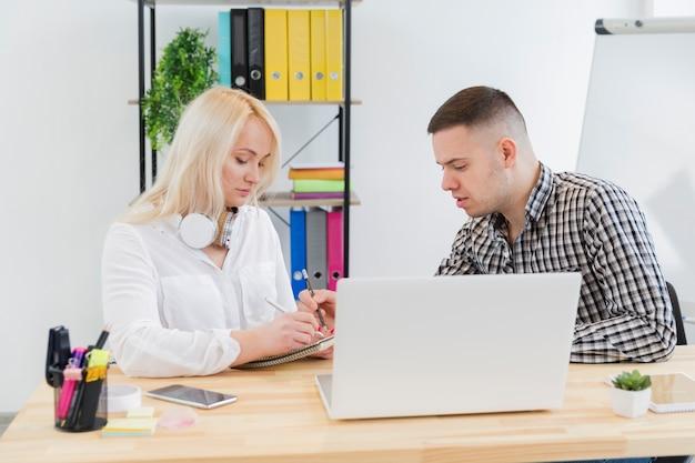 Zijaanzicht van vrouw in rolstoel en collega die bij bureau converseren