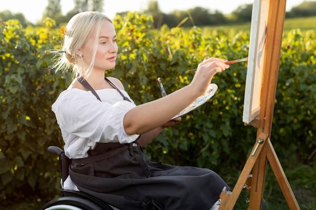 Zijaanzicht van vrouw in rolstoel met canvas en palet