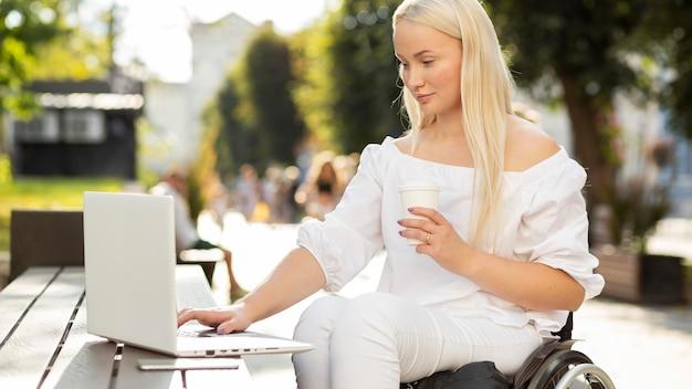 Zijaanzicht van vrouw in rolstoel met laptop buitenshuis