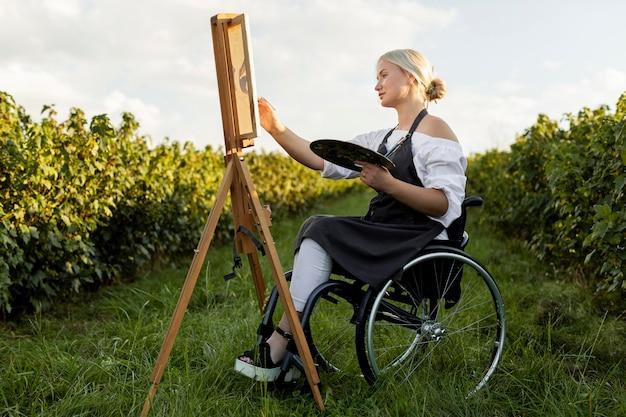 Zijaanzicht van vrouw in rolstoel met palet en canvas