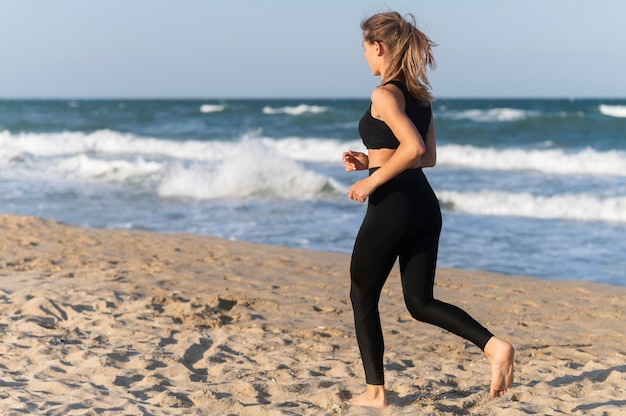 Zijaanzicht van vrouw joggen op het strand