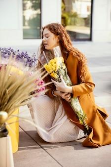 Zijaanzicht van vrouw lentebloemen buitenshuis krijgen