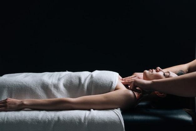 Zijaanzicht van vrouw liggend op massagetafel met gesloten ogen tijdens schouder- en nekmassage