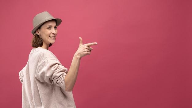 Zijaanzicht van vrouw met en hoed die stellen richten