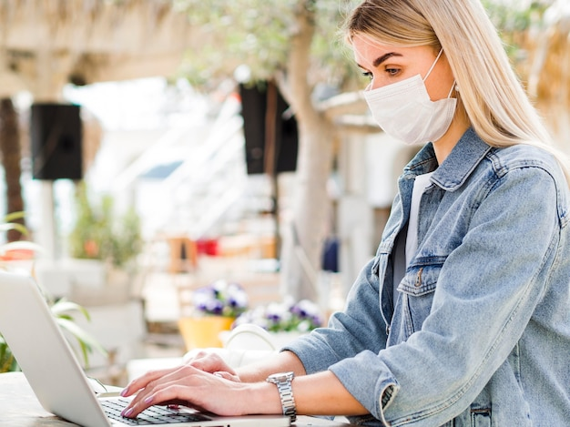 Zijaanzicht van vrouw met gezichtsmasker dat aan laptop werkt