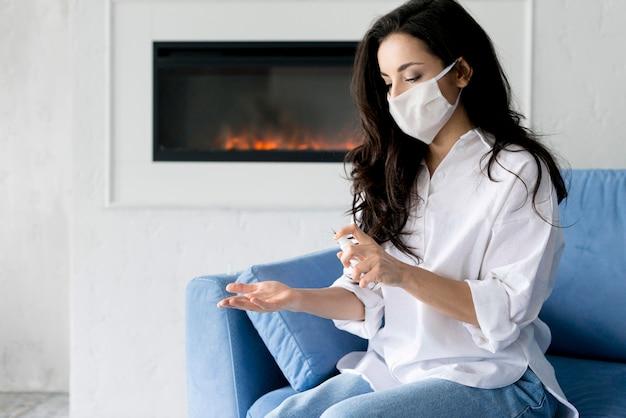 Zijaanzicht van vrouw met gezichtsmasker dat haar handen desinfecteert