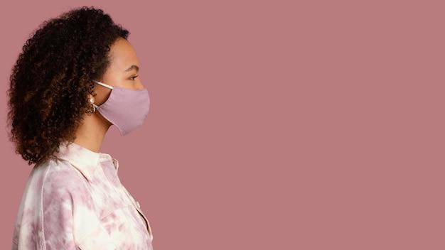 Zijaanzicht van vrouw met gezichtsmasker en exemplaarruimte
