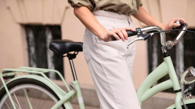 Zijaanzicht van vrouw met haar fiets buiten in de stad