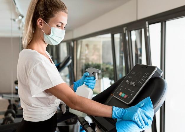 Zijaanzicht van vrouw met handschoenen en reinigingsoplossing fitnessapparatuur desinfecteren