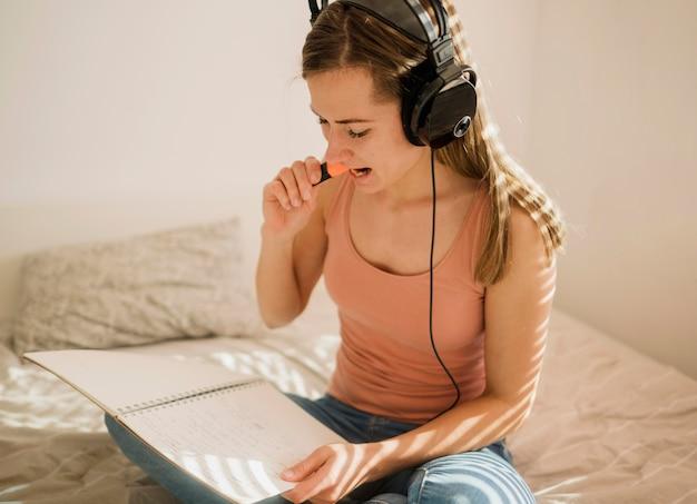 Zijaanzicht van vrouw met hoofdtelefoons in bed die teller op notitieboekje gebruiken