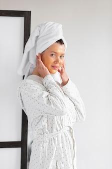 Zijaanzicht van vrouw met huidverzorging van gezicht dat badjas en handdoek draagt