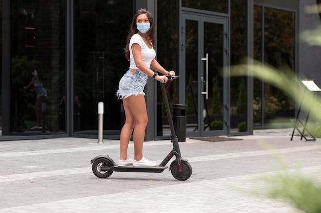 Zijaanzicht van vrouw met masker rijden op een elektrische scooter