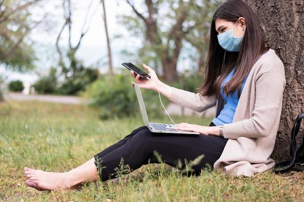 Zijaanzicht van vrouw met medisch masker die aan laptop in aard werken