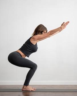 Zijaanzicht van vrouw met medisch masker die yoga doet