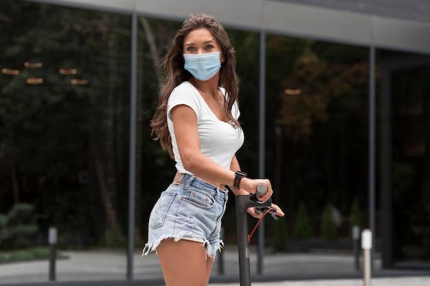 Zijaanzicht van vrouw met medisch masker elektrische autoped berijden