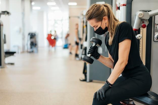 Zijaanzicht van vrouw met medisch masker en handschoenen die bij de gymnastiek uitoefenen