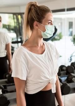 Zijaanzicht van vrouw met medisch masker in de sportschool