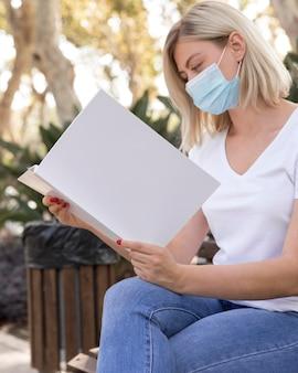 Zijaanzicht van vrouw met medisch masker leesboek buitenshuis