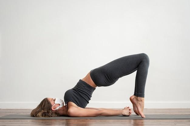 Zijaanzicht van vrouw met medisch masker thuis yoga doen