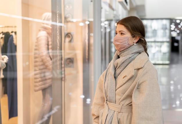 Zijaanzicht van vrouw met medisch masker window shopping