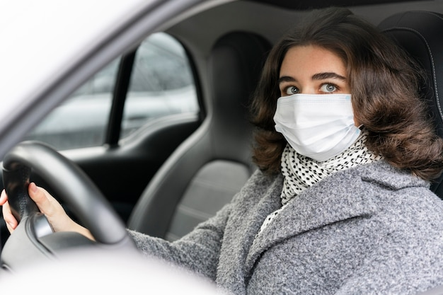 Zijaanzicht van vrouw met medische masker auto rijden