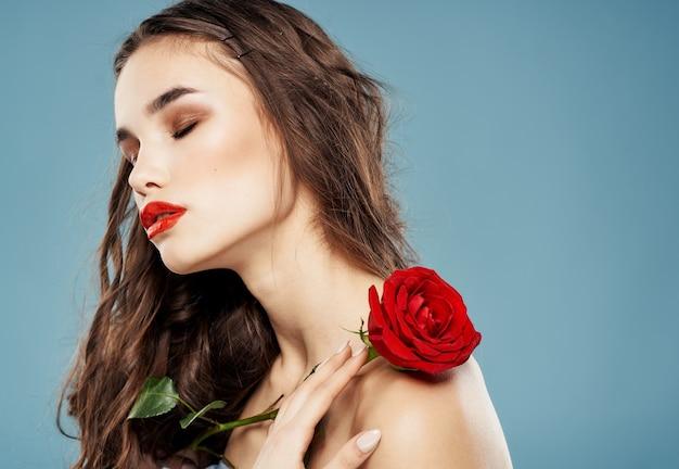 Zijaanzicht van vrouw met naakte schouders en rode bloem