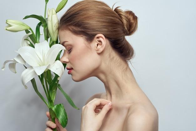 Zijaanzicht van vrouw met witte bloemen op grijze naakte schouders