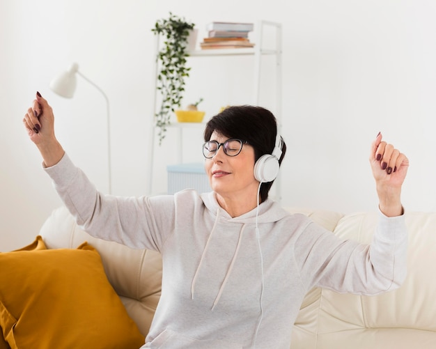 Zijaanzicht van vrouw op bank die van muziek op hoofdtelefoons genieten