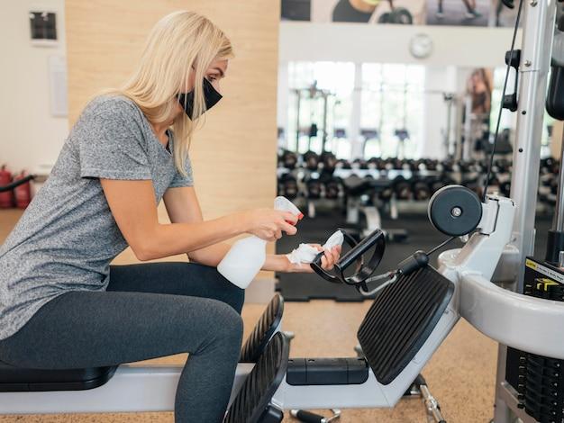 Zijaanzicht van vrouw sproeien ontsmettingsmiddel op fitnessapparatuur