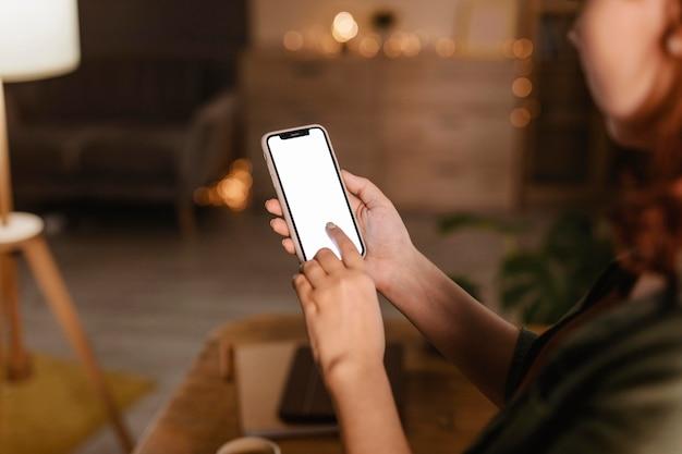 Zijaanzicht van vrouw thuis met behulp van haar smartphone