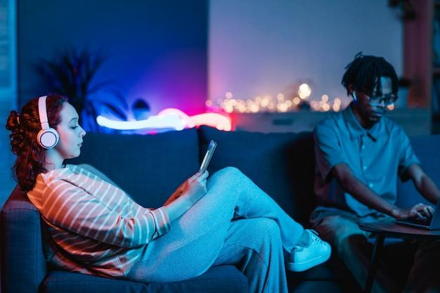 Zijaanzicht van vrouw thuis met vriendje met behulp van tablet en koptelefoon