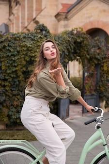 Zijaanzicht van vrouw waait kus tijdens het fietsen buiten