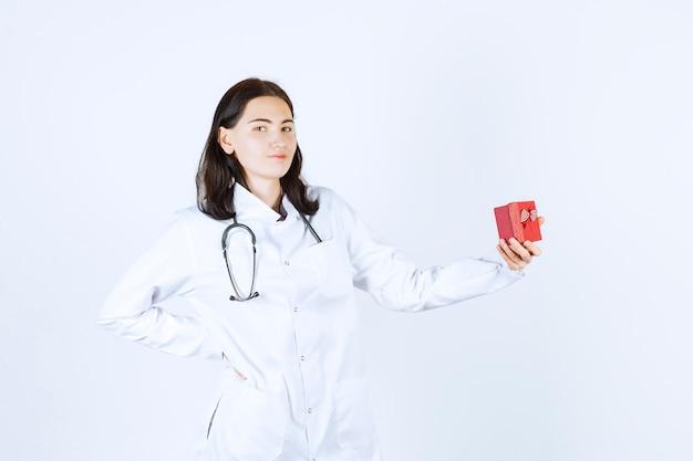 Zijaanzicht van vrouwelijke arts die haar geschenkdoos in haar hand houdt