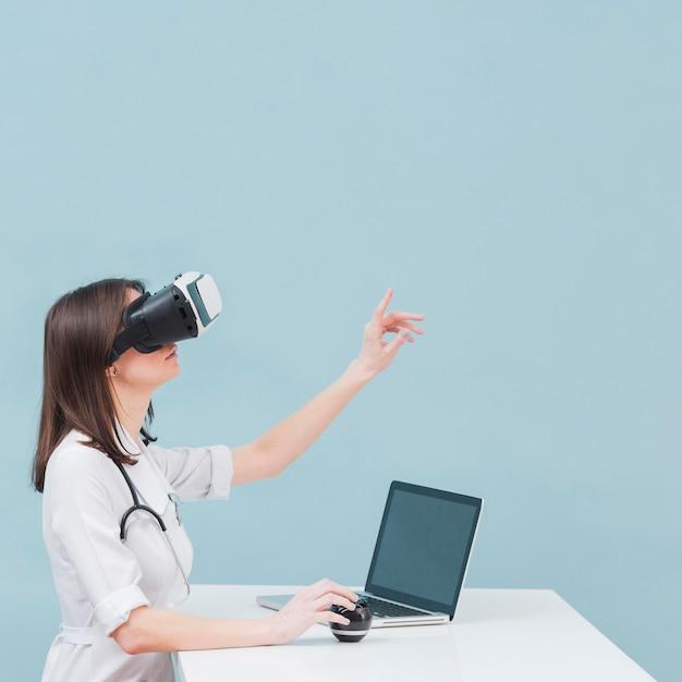 Zijaanzicht van vrouwelijke arts met virtuele werkelijkheidshoofdtelefoon en exemplaarruimte