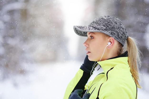 Zijaanzicht van vrouwelijke atleet, luisteren naar muziek