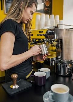 Zijaanzicht van vrouwelijke barista schuimende melk