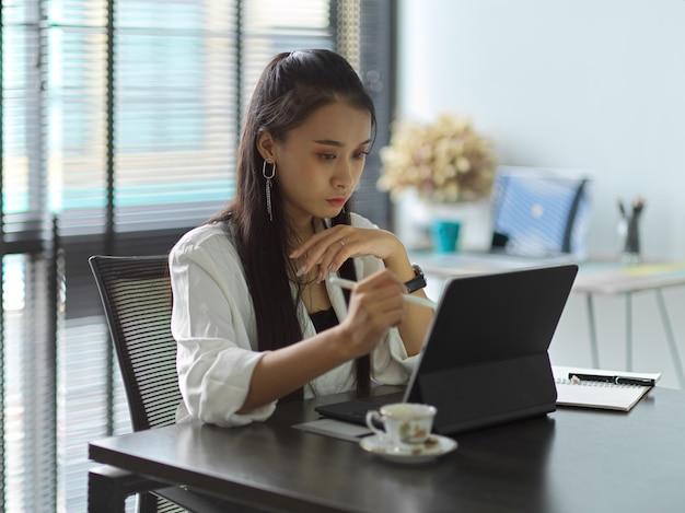Zijaanzicht van vrouwelijke beambte die met digitale tablet op werktafel in bureauruimte werkt