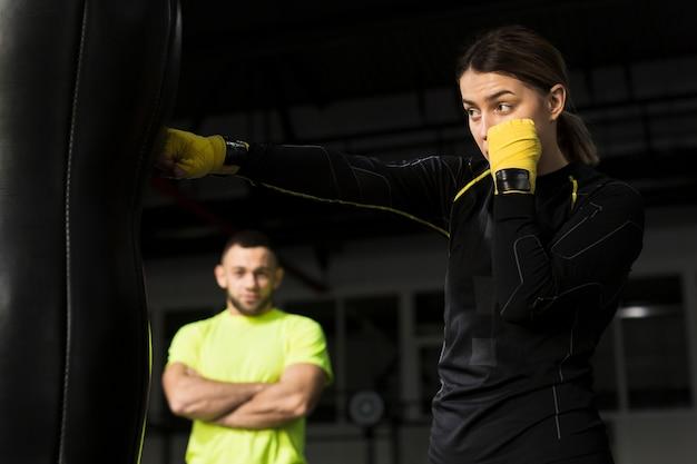 Zijaanzicht van vrouwelijke bokser met beschermende handschoenen die zware zak ponsen
