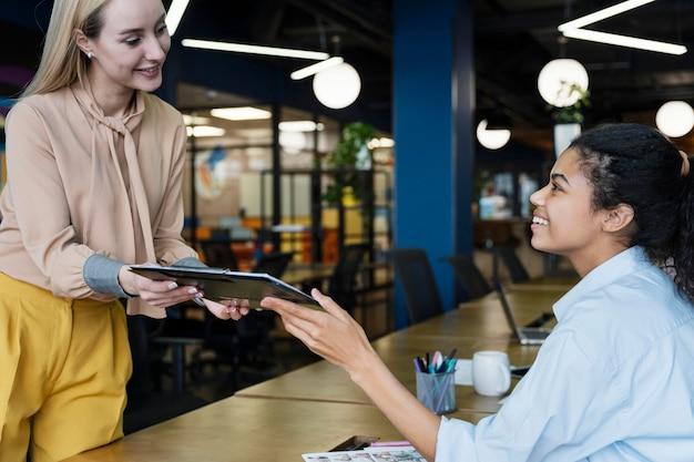 Zijaanzicht van vrouwelijke collega's die bij elkaar glimlachen en documenten delen