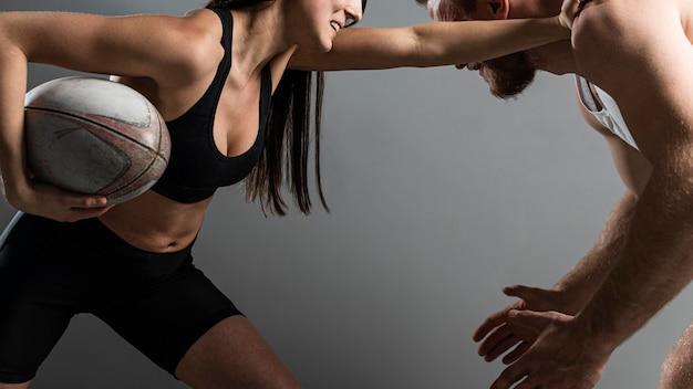 Zijaanzicht van vrouwelijke en mannelijke rugbyspelers die om bal vechten