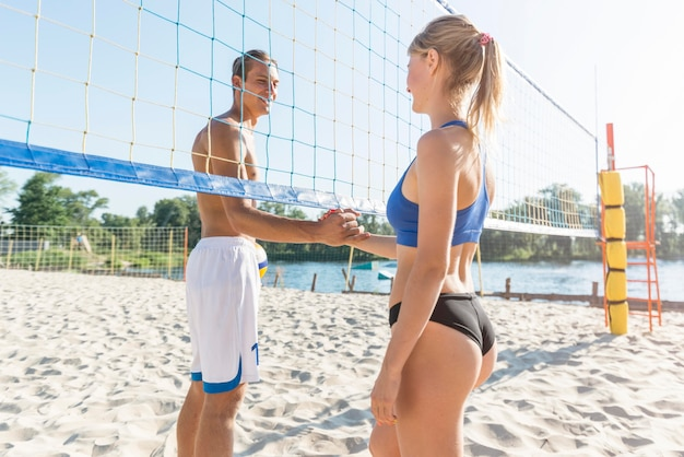 Zijaanzicht van vrouwelijke en mannelijke volleyballers schudden hand onder het net