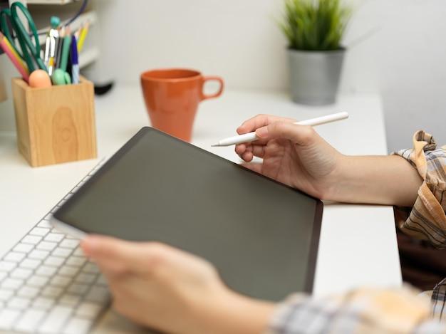 Zijaanzicht van vrouwelijke freelancer die met digitaal werkt met briefpapier en mok