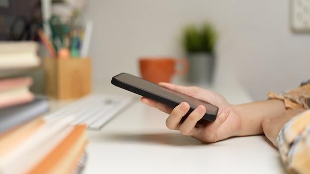 Zijaanzicht van vrouwelijke freelancer hand met smartphone op computerbureau in kantoor aan huis kamer