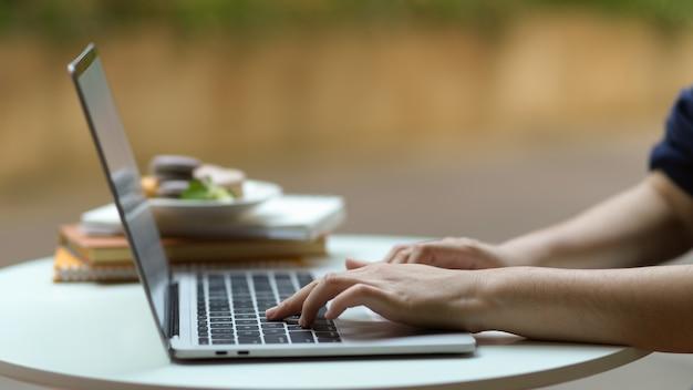 Zijaanzicht van vrouwelijke hand typen op laptop toetsenbord op koffietafel in tuin thuis