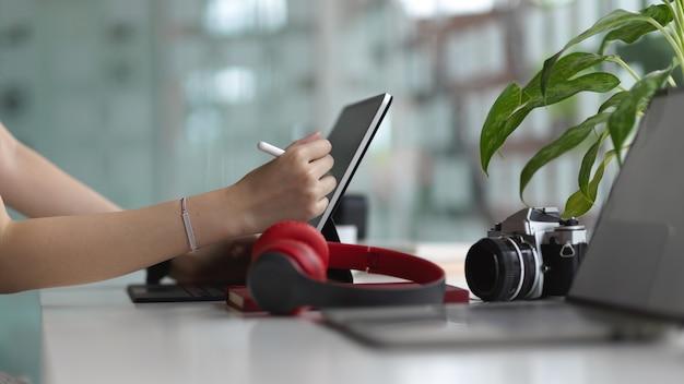 Zijaanzicht van vrouwelijke handen met behulp van digitale tablet op witte tafel in co werkruimte