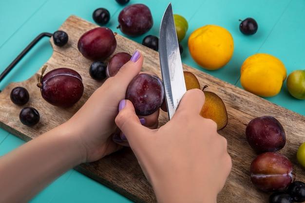 Zijaanzicht van vrouwelijke handen snijden pluot met mes en druiven bessen op snijplank en patroon van druiven nectacot pruim pluot op blauwe achtergrond