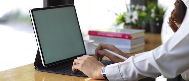 Zijaanzicht van vrouwelijke handen werken met mock-up digitale tablet op houten tafel
